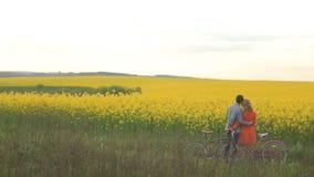 El par cariñoso adorable con las bicicletas es suavemente de abrazo y que disfruta de la naturaleza hermosa preciosa del campo cu metrajes