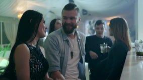 El par cariñoso comunica cerca de contador de la barra contra la perspectiva de una compañía de amigos en un club almacen de metraje de vídeo