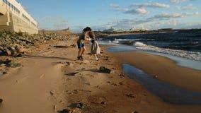 El par cariñoso corre al mar en la puesta del sol El hombre y la mujer europeos juntan jugar con uno a en la playa almacen de metraje de vídeo