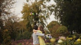 El par cariñoso en el parque lanza los globos en el cielo almacen de metraje de vídeo