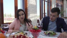 El par cariñoso en el restaurante está cenando, el individuo está alimentando a muchacha una ensalada vídeo de la cantidad de la  almacen de video