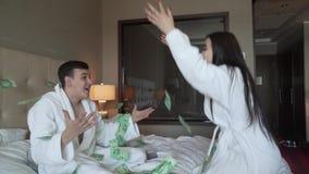 El par cariñoso en las capas blancas en cama alegre lanza para arriba el efectivo, vídeo grande de la cantidad de la acción de la metrajes