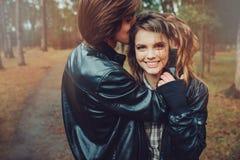 El par cariñoso feliz joven en las chaquetas de cuero abraza al aire libre en paseo acogedor en bosque fotos de archivo libres de regalías