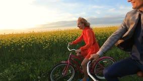 El par cariñoso feliz se está divirtiendo mientras que el montar monta en bicicleta a lo largo del campo floreciente hermoso dura metrajes