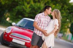 El par cariñoso feliz viaja en el coche rojo imagen de archivo libre de regalías