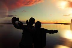 El par cariñoso hace el selfie en la puesta del sol cerca del lago Efecto de la llamarada de la lente Imagen de archivo
