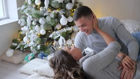 El par cariñoso miente en cama en buen humor en el fondo del árbol adornado de Navidad, mañana de la Navidad metrajes