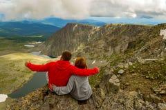 El par cariñoso que se sienta en una roca y que abraza, el hombre es pointin imagen de archivo libre de regalías