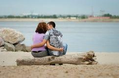 El par cariñoso se está besando en la playa del mar Fotografía de archivo libre de regalías