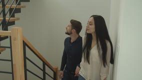 El par caucásico joven sube las escaleras que llevan a cabo las manos que miran alrededor un apartamento nuevo-comprado que es ex almacen de metraje de vídeo