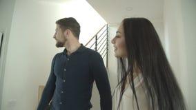 El par caucásico milenario sube las escaleras que llevan a cabo las manos que miran alrededor una casa nuevo-comprada que es exci almacen de metraje de vídeo