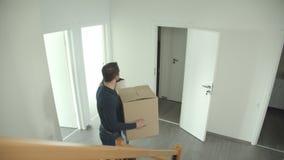 El par caucásico sube las escaleras con la caja de cartón en la mudanza a una nueva casa que es feliz y excitada almacen de metraje de vídeo