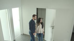 El par caucásico sube las escaleras que celebran las manos y las miradas alrededor en un nuevo apartamento que es feliz almacen de video