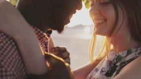 El par caucásico y africano que se besa y que mira en cada otros observa almacen de video