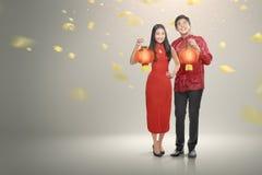 El par chino feliz en cheongsam viste sostener las linternas rojas fotos de archivo libres de regalías