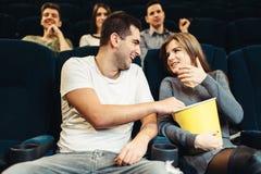 El par come las palomitas mientras que mira película en cine Fotografía de archivo libre de regalías