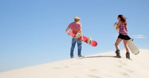 El par con la arena sube a mirar una distancia en el desierto 4k almacen de video