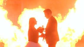 El par con el maquillaje para Halloween en un partido, un fuego enorme está quemando cerca almacen de metraje de vídeo