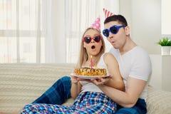 El par con una torta con las velas felicita por su cumpleaños encendido Imagen de archivo