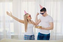 El par con una torta con las velas felicita por su cumpleaños encendido Foto de archivo libre de regalías