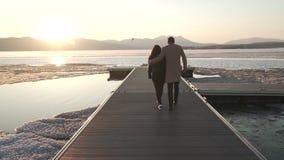 El par congelado pero feliz en amor camina en el embarcadero en el vídeo de la cantidad de la acción de la puesta del sol almacen de video