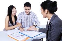 El par consulta con el agente, firmando papeleo Imágenes de archivo libres de regalías