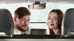El par da vuelta a sus caras al asiento trasero dentro del coche almacen de metraje de vídeo