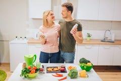 El par de amor feliz del vegano sostiene las botellas con el smoothie natural mientras que cocina verduras crudas en la cocina bl foto de archivo libre de regalías