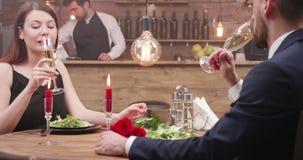 El par de amor se sienta en una tabla en un champán del restaurante y de la bebida metrajes