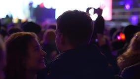 El par de baile atractivo mira en amor uno a en una muchedumbre de gente en concierto en fondo de una escena borrosa almacen de metraje de vídeo