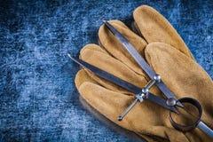 El par de construcción contornea los guantes protectores de cuero en meta Fotos de archivo