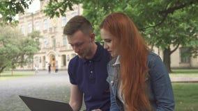 El par de estudiantes discute algo en el ordenador portátil en campus metrajes