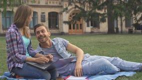 El par de estudiantes ejercita en el césped en campus fotografía de archivo