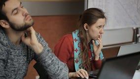 El par de gente trabaja en oficina en los ordenadores portátiles que se sientan en la tabla de madera almacen de video