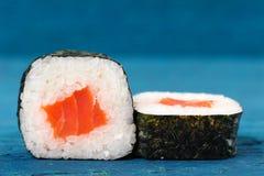 El par de japonés rueda con los salmones, el arroz y el nori en vagos del azul de cielo Fotografía de archivo