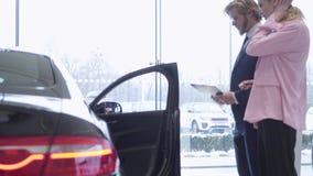 El par de Jouful elige un nuevo vehículo en una concesión de coche Sala de exposición del coche almacen de metraje de vídeo