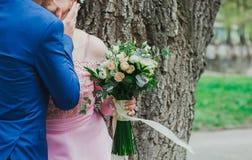 El par de la boda se besa cerca del árbol en el bosque o el parque verde La novia del tamaño extra grande en vestido rosado del c imágenes de archivo libres de regalías