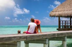 El par de la luna de miel se sienta en un embarcadero de madera en las islas de Maldivas Imagenes de archivo
