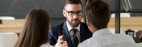 El par de la vista posterior resuelve con agente inmobiliario o el agente inmobiliario foto de archivo libre de regalías