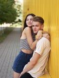 el par del Caída-en-amor está abrazando en un fondo amarillo de la pared Principio de una historia de amor Sensaciones, concepto  Imagen de archivo libre de regalías