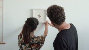 El par del inconformista cuelga el marco en nueva casa almacen de video