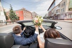 El par del recién casado está conduciendo un convertible Imagen de archivo