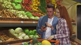 El par discute la lista de compras en smartphone en el supermercado metrajes