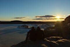 El par disfruta de puesta del sol sobre el glaciar imágenes de archivo libres de regalías