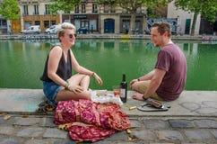 El par disfruta del almuerzo en los bancos del canal San Martín en París Fotos de archivo libres de regalías