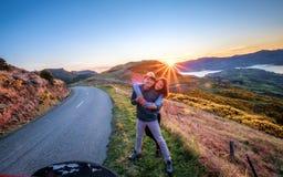 El par disfruta del paisaje hermoso de Akaroa cerca de Christchurch en Nueva Zelanda fotos de archivo