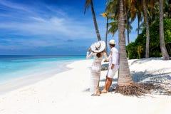 El par disfruta del tiempo de vacaciones de verano en una playa tropical fotos de archivo libres de regalías