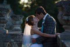 El par dulce se está besando en el medio de los floreros antiguos Fotografía de archivo
