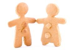 El par, el muchacho y la muchacha del pan de jengibre se apelmaza juntas llevando a cabo las manos Imagen de archivo