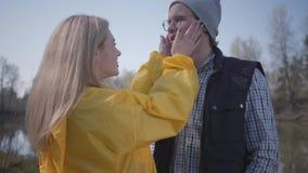 El par elegante cerca del r?o en el movimiento rubio de la muchacha del bosque sirve la barba Chaleco que lleva del hombre, sombr almacen de metraje de vídeo